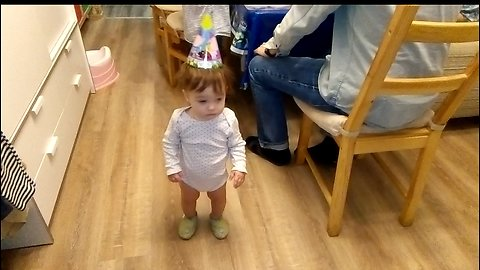 Cute baby does not know what to do on his own birthday.