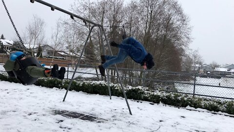 Dad does backflip off swings while son watches on