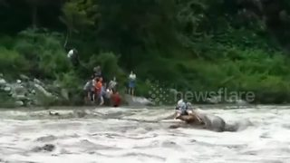 Rescuers save two tourists trapped in flooded river - Video
