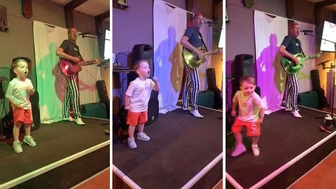 Aspiring 3-year-old star jumps on stage to steal the show from actual performer, resulting in a full house crowd erupting into laughter