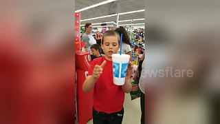 Boy performs floating cup magic trick in supermarket - Video