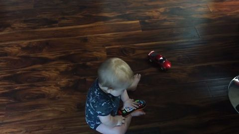 Cute Baby Chases Toy Car Around In Circles