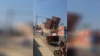 Demolition accident as building falls wrong way and crushes excavator - Video