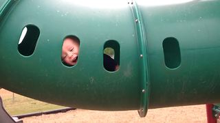 Cute Little Boy Plays Peek A Boo At Playground - Video