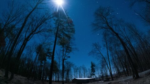 Moon and star night lapse from forest mountain cabin