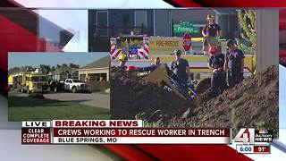 Crews work to rescue worker in trench - Video