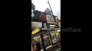 Man leaps from bus shelter into crowd celebrating England win