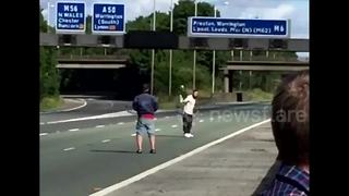 Men play tennis on UK motorway with traffic at standstill - Video