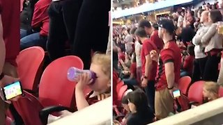 Football Fan Holds Phone Behind His Back So Daughter Can Watch Cartoons - Video