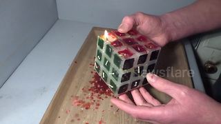 Man solves burning candle Rubik's Cube - Video
