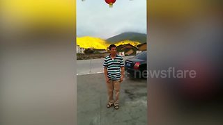 Chinese tourists pose in front of 'golden mountain' - Video