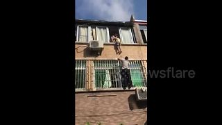 Neighbours rescue girl hanging from second-floor window - Video