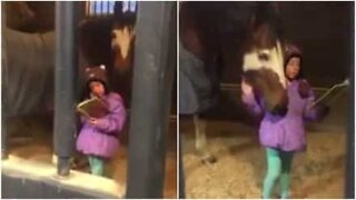 Adorable girl reads horse a story every day