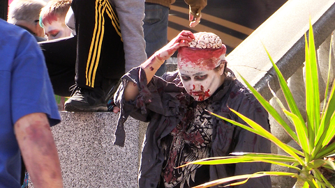 Zombie picks brain and eats it at Halifax Zombie Walk