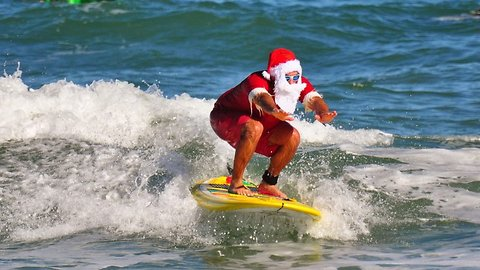 Jingle all the wave! Grandfather raised over $100,000 (£80k) for charity after turning fun family santa surfing into worldwide event