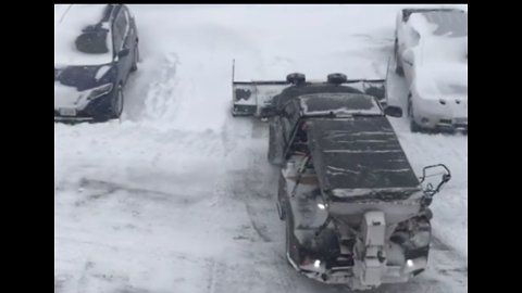 Plow Clears Parking Lot in Snow-Covered Stevens Point