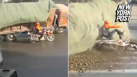 Motorcyclist narrowly avoids getting obliterated by a mountain of debris
