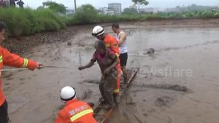 Firefighters rescue elderly woman trapped in muddy pond - Video