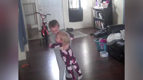 A Young Boy Dances With His Little Sister In His Arms