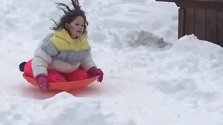 Little girl sleds down hill onto a table and falls off!