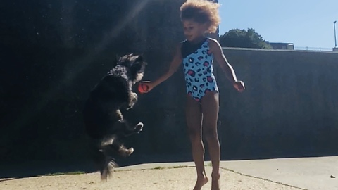 Girl and doggy jump together at the same time