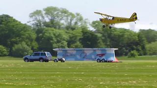 Stunt plane successfully lands on a moving trailer