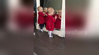 Adorable twins play with reflections in mirror