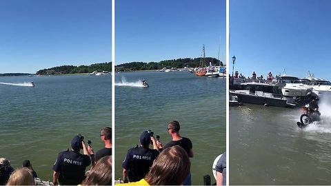 Riding on a wave! Man rides his motorbike across water