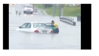 Woman Rescued From Car Swept Up in Floodwaters - Video