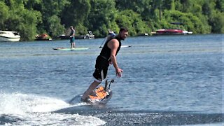 Man skillfully rides a futuristic jet powered surf board