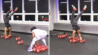 Incredible athlete walks on hands while balancing on rolling dumbbells