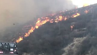 Cars Drive Through Burning Hills North of Los Angeles - Video
