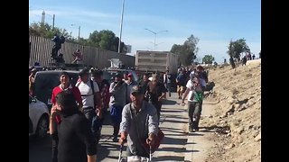 Migrants Vault Over Highway Fence in Tijuana After US Federal Authorities Launch Tear Gas - Video