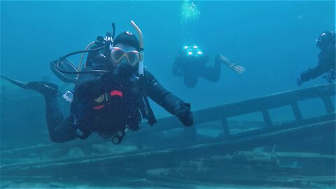 Imaginative scuba driver mimes a comical explanation of a historic shipwreck