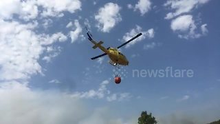 Helicopters race to pick up water to fight wildfires in Spain - Video