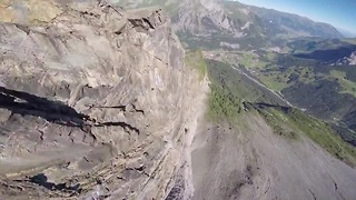 Wingsuit pilot jumps from mountain's edge - Video