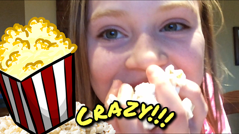 Little girl stuffs her face with popcorn!