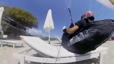 Red-faced paraglider crashes into sun loungers while trying to impress wife