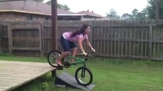 A Woman Rides A Bike Up A Ramp And Falls - Video