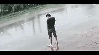 Man relieving himself on road splattered when lorry passes by