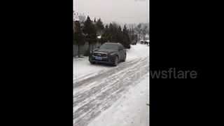SUV slides dangerously down snow-covered slope in China - Video