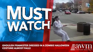 Ghoulish prankster dressed in a zombie Halloween costume almost falls - Video