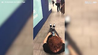 Young man rides skateboard lying down in London tube station