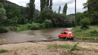 Vintage Fiat courageously crosses challenging river
