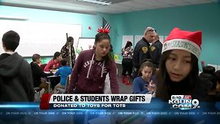 Police and students wrap gifts for toys for tots - Video