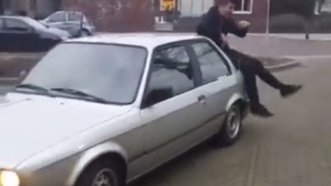 Guy goofing around on top of car receives instant karma