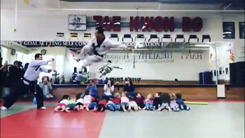 Tae Kwon Do master leaps over 16 children and breaks board