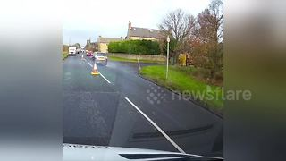 Driver nearly hits oncoming car on partially closed road - Video