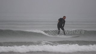 Surfer battles heavy rainfall at Benone beach, Northern Ireland - Video