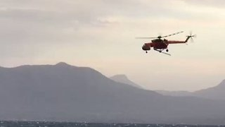 Greek Firefighters Near Kalamos Use Helicopter To Tackle Wildfire - Video